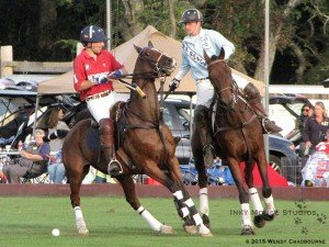 Two polo players competing for the ball